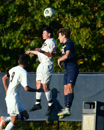 CARL RUSSO/Staff photo Windham's Jackson Mahoney, right and Timberlane's Kelley Donovan head the ball in boys soccer action. 10/15/2019