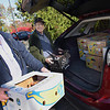 TIM JEAN/Staff photo<br /> <br /> John Tierney, left, of North Andover, and Stuart McNeil, of Andover, pack an SUV with food donations from the North Andover Stop & Shop.  10/24/19