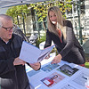 TIM JEAN/Staff photo<br /> <br /> Peter McSwiggin, left, listens to Michelle Iturralde, who's son Anthony managers the Vivint Solar booth, on the last day of the season for Andover's Farmers Market.  10/19/19