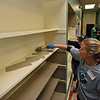 "RYAN HUTTON/ Staff photo<br /> Timberland employee Rebecca Conway paints a built in shelving unit at the Bread & Roses soup kitchen on Newbury Street in Lawrence during the company's ""Serv-a-Palooza"" community service event on Wednesday."