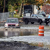 RYAN HUTTON/ Staff photo<br /> A car attempts to ford a flooded Market Street in Lawrence next to the O'Connell South Common on Thursday morning as two other vehicles turn back.