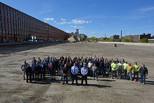 RYAN HUTTON/ Staff photo<br /> Developer Sal Lupoli, center, stands with his dozens of his employees, contractors and associates in the location between the Merrimack River and the old Wood Mill in Lawrence that will soon be home to a multi level parking garage.
