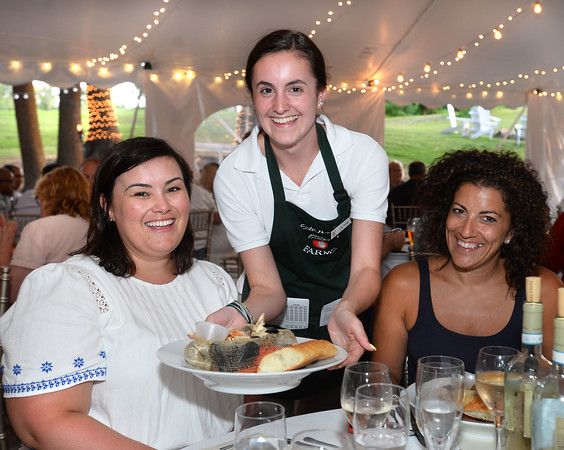 """CARL RUSSO/Staff photo. Smolak Farms waitress, Olivia Bertolino serves a traditional clam bake dish to Ashley Dogramacian, left of Peabody and Cori Saragas of Andover. Bertolino is from North Andover. <br /> <br /> Smolak Farms holds a weekly """"pop up"""" dining experience every Wednesday evening through the summer. The farm invites New England chefs to cook a multi-course dinner in the Smolak Farms Pine Grove using produce grown at the farm, creating their menus on a """"WHIM."""" Executive chef Nick Deutmeyer of Post 390 in Boston's Back Bay was featured on July 10.     7/10/2019"""