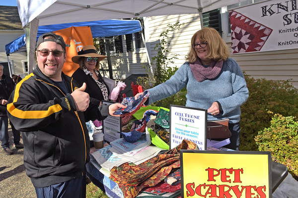 TIM JEAN/Staff photo<br /> <br /> Mike Squillacioti, left, of Andover, buys a scarf for his dog from Maureen  Pritzker, of Knit One, Sew 2, on the last day of the season for Andover's Farmers Market held at the Andover Center for History & Culture on Main Street. The market will open next year in a new location at South Church. 10/19/19