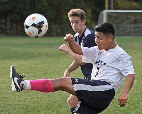 MIKE SPRINGER/Staff photo<br /> Lawrence's Samuel De Amorin kicks the ball as Ryan O'Sullivan of Andover applies defensive pressure during varsity soccer action Tuesday at Andover.<br /> 10/01/2019