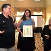 "RYAN HUTTON/ Staff photo <br /> Ralph Sinclair, left, owner of Woof Woof Doggie Daycare and Boarding, jokes with Eagle-Tribune publisher Karen Andreas, right, as he and his daughter Kaytlin, center, accept the Best of the Eagle-Tribune Award for ""Best Pet Daycare"" during the awards breakfast at the Atkinson Country Club on Wednesday morning."