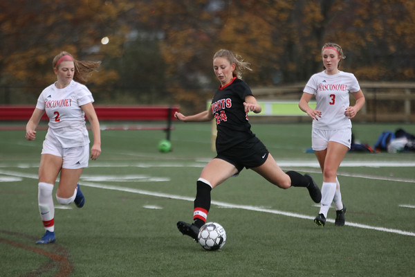 MIKE SPRINGER/Staff photo<br /> North Andover's Olivia Gotobed, center, kicks the ball upfield under defensive pressure from Ryenne Feeney, left, and Charlotte Meixsell of Masconomet during varsity soccer play Monday in North Andover.<br /> 10/28/2019