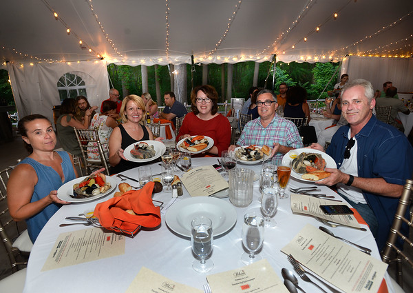 """CARL RUSSO/Staff photo. From left, Gloria Couillard of Pelham N.H., Krista Munsie of Plaistow N.H., Elizabeth Keegan of Salem Ma., Michael Tannian of Haverhill and Beau Vanderford of Salem Ma.  ready to enjoy the main course of the clam bake.  <br /> <br /> Smolak Farms holds a weekly """"pop up"""" dining experience every Wednesday evening through the summer. The farm invites New England chefs to cook a multi-course dinner in the Smolak Farms Pine Grove using produce grown at the farm, creating their menus on a """"WHIM."""" Executive chef Nick Deutmeyer of Post 390 in Boston's Back Bay was featured on July 10. 7/10/2019"""