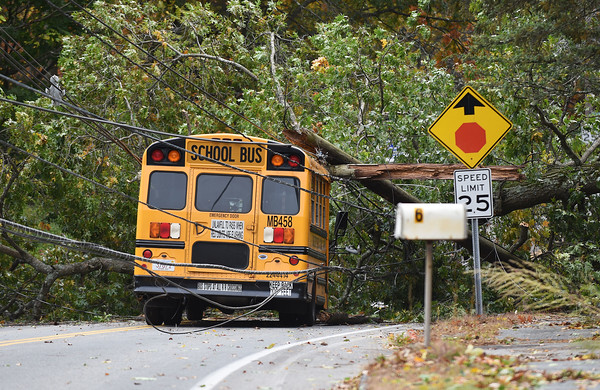 RYAN HUTTON/ Staff photo<br /> A Lawrence Public Schools bus sits trapped under a fallen tree and power lines on North Street at Chandler Road on Thursday morning. Only the driver was onboard at the time and escaped any serious injury.