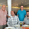 """CARL RUSSO/Staff photo. Michael Smolak, standing left, owner of Smolak's Farms in North Andover and his partner Bill DeRosa, standing right, greet representatives of 110 Grill restaurants, Dan Greenough, left and Elliot Williams during the WHIM dining experience on July 10. <br /> <br /> Smolak Farms holds a weekly """"pop up"""" dining experience every Wednesday evening through the summer. The farm invites New England chefs to cook a multi-course dinner in the Smolak Farms Pine Grove using produce grown at the farm, creating their menus on a """"WHIM."""" Executive chef Nick Deutmeyer of Post 390 in Boston's Back Bay was featured on July 10. 7/10/2019"""