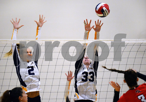 CARL RUSSO/Staff photo Andover's Jodi Parrot, left and Marissa Kobelski defend the net. The North Andover Scarlet Knights played against the Andover Golden Warriors in volleyball action Monday night. 10/21/2019