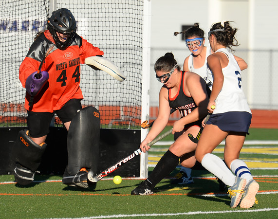 CARL RUSSO/Staff photo With less than a minute to play, North Andover's goalie, Jenna Bard makes the save as her teammate, Kiki Valentino clears the ball while Andover captain, Hanna Medwar rushes in attempting the rebound. Andover and North Andover battled to a 1-1 tie in field hockey action Wednesday afternoon.10/23/2019