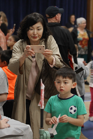 MIKE SPRINGER/Staff photo<br /> Sunny Lee photographs her grandson Grayson, a kindergartner, during the Family STEM (Science, Technology, Engineering and Mathematics) Night on Thursday at St. Michael School in North Andover.<br /> 10/03/2019