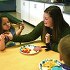 RYAN HUTTON/ Staff photo<br /> Whittier Tech student Brooke Gates, 17, interacts with Laura Gould, 4, left, and Liam Fay, 3, right, during lunch time at Whittier's new early childhood education center established through a partnership with the YMCA.