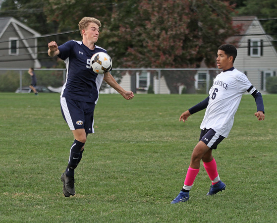MIKE SPRINGER/Staff photo<br /> Andover's Jackson Gress, left, redirects the ball as Jesus Guzman of Lawrence looks on Tuesday during varsity soccer action at Andover.<br /> 10/01/2019