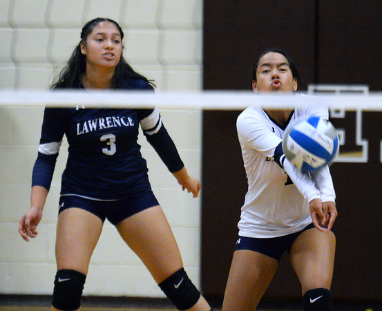 CARL RUSSO/Staff photo Lawrence's Yoneli Batista returns the serve as Marjorie Martinez stands by to help. Haverhill defeated Lawrence in volleyball action wednesday evening. 10/9/2019