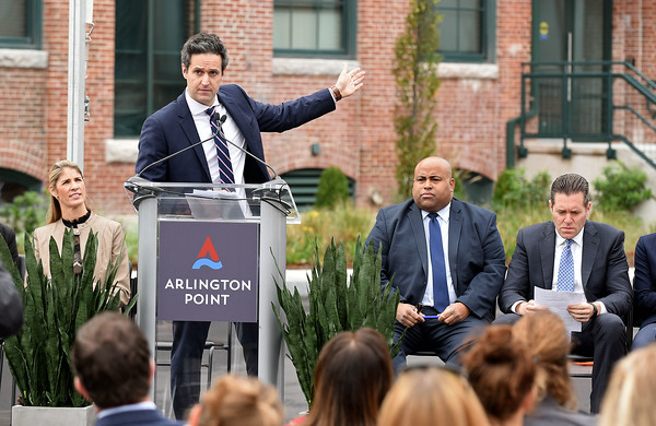 RYAN HUTTON/ Staff photo <br /> Dan Drazen, vice president of development for Trinity Financial, gestures to the newly renovated Arlington Point apartments on Broadway in Lawrence at the site of the old Van Brodie Mill building on Tuesday.  At left are Congresswoman Lori Trahan and at right are Lawrence Mayor Daniel Rivera and state Sen. Barry Finegold.