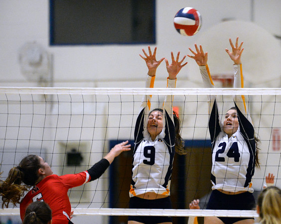CARL RUSSO/Staff photo Andover's Brooke Abouhamad, left and Abby  Ledoux reach high to defend as North Andover's Deanna Bosco spikes the ball. The North Andover Scarlet Knights played against the Andover Golden Warriors in volleyball action Monday night. 10/21/2019