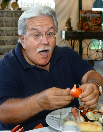 """CARL RUSSO/Staff photo.  Bill Galatis of Lynnfield cracks a lobster claw from his clam bake dish that included little necks, mussels, rock crab and pearl potatoes. <br /> <br /> Smolak Farms holds a weekly """"pop up"""" dining experience every Wednesday evening through the summer. The farm invites New England chefs to cook a multi-course dinner in the Smolak Farms Pine Grove using produce grown at the farm, creating their menus on a """"WHIM."""" Executive chef Nick Deutmeyer of Post 390 in Boston's Back Bay was featured on July 10. 7/10/2019"""