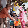 TIM JEAN/Staff photo<br /> <br /> Pricilla Cox, left, of Depot Antiques passes out candy to children during the Downtown Business Trick-or-Treating in Derry.  10/26/19