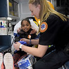 TIM JEAN/Staff photo<br /> <br /> Jade Ramirez, 8, of Lawrence, checks out the inside of an ambulance as Lawrence General Hospital EMT Meghan Litch puts safety gloves on her during Lawrence Fire Department open house Saturday morning.   10/12/19
