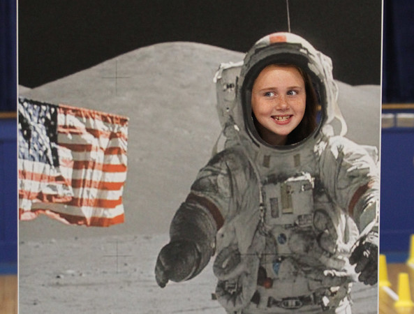 MIKE SPRINGER/Staff photo<br /> Sixth-grader Hannah Harrington looks out from a photograph of a NASA astronaut walking on the moon during the Family STEM (Science, Technology, Engineering and Mathematics) Night on Thursday at St. Michael School in North Andover.<br /> 10/03/2019