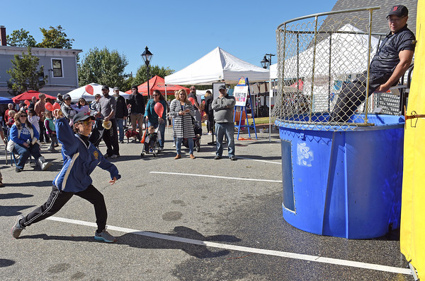 TIM JEAN/Staff photo<br /> <br /> State Rep Linda Dean Campbell, left, trows a ball to dunk State Rep Frank Moran, during the second annual Methuen Day in downtown Methuen.  10/5/19