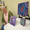 TIM JEAN/Staff photo<br /> <br /> Artist Rebecca M. Jones, of Haverhill, relaxes by her work on display in the Merrimack Valley Music & Arts Pop-up Art Gallery during the first annual Art Walk throughout downtown Haverhill.    9/14/19
