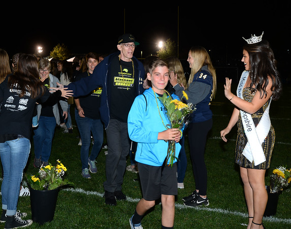 CARL RUSSO/Staff photo Windham students and Miss New Hampshire 2019, Sarah Tubbs of Sandown form two lines as they greet cancer survivors and their families with flowers while they walk onto field. <br /> <br /> The 9th Annual Windham high Jaguar Blackout Cancer Football Game was held Friday night on September 27. <br /> <br /> Windham grown Project Blackout kicks off a series of events around the town to generate awareness of pediatric cancer and raise funds to support research efforts and care for the children and families currently battling pediatric cancer in Windham. Students performed at the football game halftime show dedicated to families who have been helped by the project. 9/27/2019