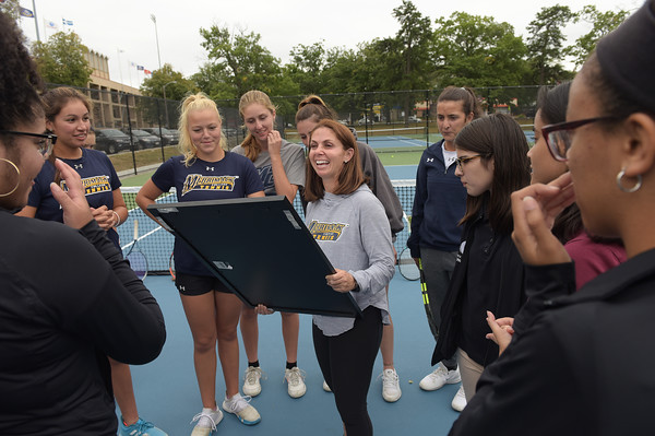 TIM JEAN/Staff photo<br /> <br /> Members of the Lawrence High School girls tennis team presented a thank you gift to Merrimack College tennis players and coach Dena Madden, center, for their help and support during last season.    9/12/19
