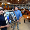 CARL RUSSO/staff photo. READING MAG: Lobster Claw owners, Victor Gresek, left and his brother, Luke hold a painting created from a photo of their father, Harry in 2015 during a fishing trip in Maine. Their father started the business in 1976. <br /> <br /> The Lobster Claw, a North Reading family owned restaurant since 1976 was Started by Harry Gresek. His sons, Victor Gresek and Luke Gresek continue the family business after Harry's passing. The two brothers took over three years ago. The restaurant is known for its chowders and sauces and fresh seafood. 9/12/2019