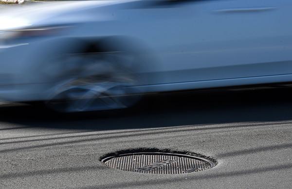 RYAN HUTTON/ Staff photo <br /> Cars avoid sunken-in manhole covers on Salem Street in Haverhill on Friday.
