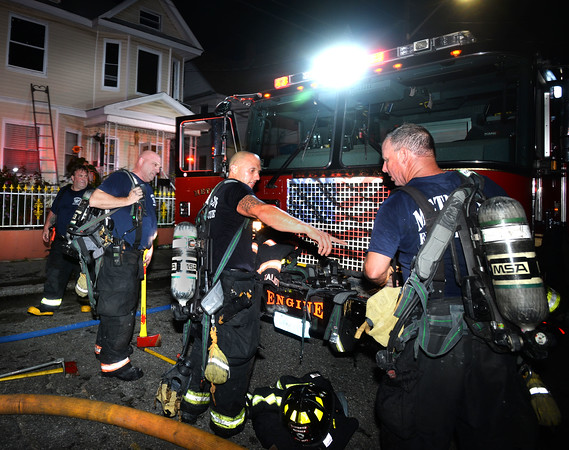 CARL RUSSO/Staff photo. Methuen firefighters take a break after battling the fire on the second floor. Quick action by the Methuen fire dept. prevented a single alarm fire from destroying a two family home on 12-14 Carlton Street Thursday night. <br /> <br /> Firefighters battled the fire from inside in the rear of the second floor, which had the most interior damage, allowing them to save the structure. <br /> <br /> Residents were out of the building as firefighters arrived, although three were taken to the hospital for minor injuries and evaluation.  9/19/2019