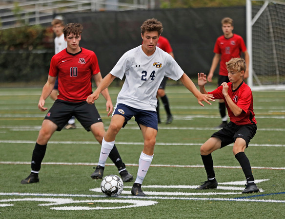 MIKE SPRINGER/Staff photo<br /> Andover's Anthony Previte, center, controls the ball under as William Gossman, left, and Jonathan Bono of North Andover look during varsity soccer action Thursday at North Andover.<br /> 9/26/2019