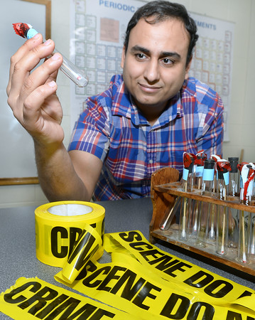 CARL RUSSO/Staff photo. Michael Mankarios of Haverhill holds an evidence test tub and other items found in a Forensic Science class. <br /> <br /> Michael Mankarios, who immigrated to the United States from Egypt six years ago with only $200 to his name, recently graduated from Northern Essex Community College with an associate's degree in criminal justice. He won a full boat scholarship to UMass Boston. 9/12/2019