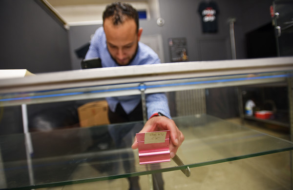 RYAN HUTTON/ Staff photo <br /> Robert Diaz, owner of Mr Hookah on Broadway in Methuen, removes the last bit of vaping merchandise from his store's display case on Thursday after Gov. Charlie Baker declared a public health emergency and banned the sale of vaping merchandise and e-cigarettes until January.