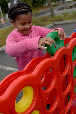 TIM JEAN/Staff photo<br /> <br /> Haddasah Encarnacion, 7, of Lawrence plays an over size game of connect four during a Community Spirit celebration at the Stadium Plaza on Winthrop Avenue in Lawrence.   9/14/19
