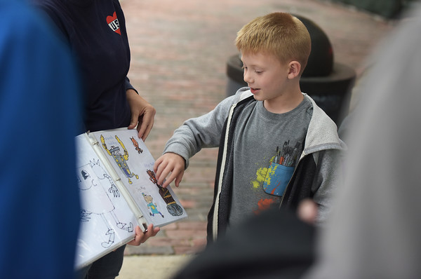 TIM JEAN/Staff photo<br /> <br /> Artist Andrew Pelczar, 7, of Haverhill, talks about his drawings as his mother Colleen holds them for a crowd of onlookers during the first annual Art Walk throughout downtown Haverhill. The event featured local artists painting around the city streets, open studios, demonstrations and performances at a dozens businesses.    9/14/19
