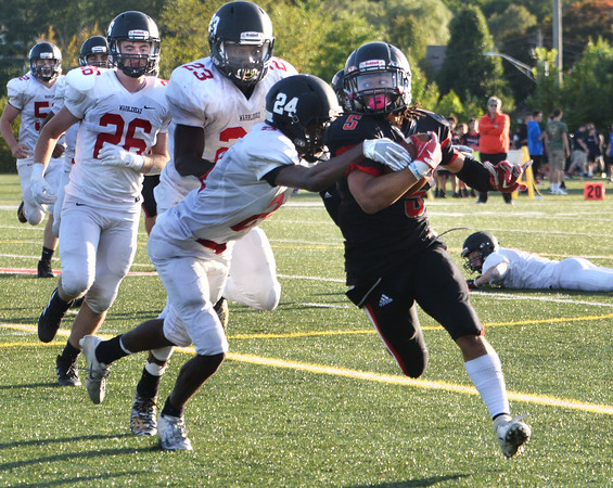 CARL RUSSO/Staff photo. North Andover captain, Freddy Gabin sweeps around Marblehead's Godot Gaskins and  breaks the tackle. Marblehead defeated North Andover 25-20 in Friday football action. 9/12/2019