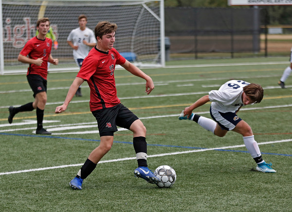 MIKE SPRINGER/Staff photo<br /> North Andover's Max Callamaro, left, maintains control of the ball as Aidan Magner of Andover struggles to keep his balance after an attempted steal during varsity soccer action Thursday at North Andover.<br /> 9/26/2019
