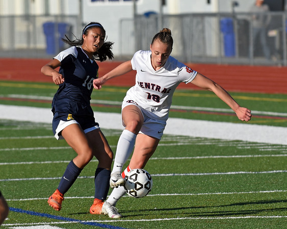 RYAN HUTTON/ Staff photo <br /> Central Catholic's Kaleigh Lane dribbles the ball away from Andover's Annabelle Chan during Thursday's game at Andover High School.