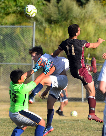 CARL RUSSO/Staff photo. Whittier's NateCartier fights to head the ball in front of Minuteman's goalie and defender. Cartier had two goals in the game. Whittier Tech. defeated the Minuteman 3-0 in boys soccer action Monday afternoon. 9/16/2019