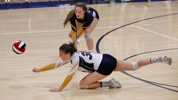 MIKE SPRINGER/Staff photo<br /> Andover's Tatum Shaw dives for the ball as teammate Jenny McNaughton looks on during varsity volleyball play Monday against Central Catholic at Andover.<br /> 9/23/2019