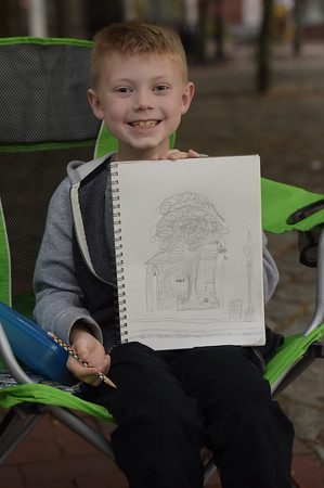 TIM JEAN/Staff photo<br /> <br /> Artist Andrew Pelczar, 7, of Haverhill, shows off his work in progress on his drawing during the first annual Art Walk throughout downtown Haverhill. The event featured local artists painting around the city streets, open studios, demonstrations and performances at a dozens businesses.    9/14/19
