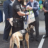 TIM JEAN/Staff photo<br /> <br /> K-9 Officer Carlos Aguirre, left, and his partner Magnus, receive a goodie bag from Stephen Isherwood, Director of Bulger Animal Hospital during a ribbon cutting ceremony outside the new location in Lawrence.    9/25/19