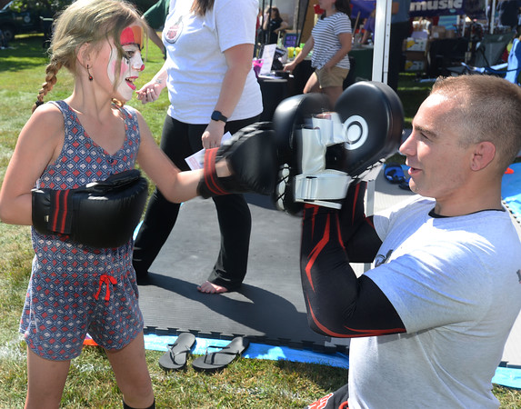 CARL RUSSO/Staff photo. Danika Nault of Epsom N.H. boxes with Jon Paul, martial arts instructor for Limitless Pride, martial arts and fitness center in Auburn. <br /> <br /> The 30th annual Derryfest was held Saturday in MacGregor Park. The park was full of booths, entertainment on stage, businesses under tents etc. The  300th anniversary of Nutfield  time capsule and its contents was on display at the Derry Heritage Commission booth.  9/21/2019
