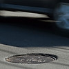 RYAN HUTTON/ Staff photo <br /> Cars avoid sunken-in manhole covers on Salem Street in Haverhill on Friday.
