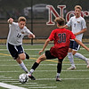 MIKE SPRINGER/Staff photo<br /> Andover defenseman Ryan O'Sullivan, left, tries to move past Caleb Ginsburg of North Andover as O'Sullivan's teammate Jackson Gress looks on during varsity soccer action Thursday at North Andover.<br /> 9/26/2019