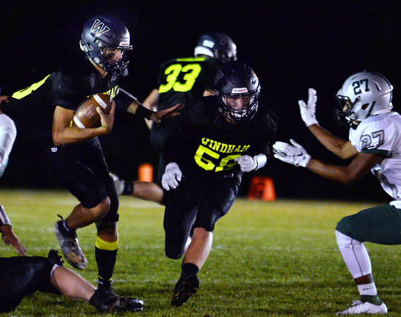 CARL RUSSO/Staff photo. Windham's James Comeau blocks for Rocky Heres as he picks up more yardage.  Windham football action against Manchester Central. 9/27/2019
