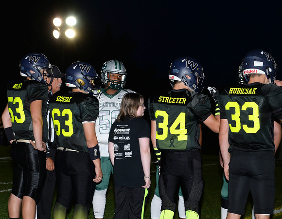 CARL RUSSO/Staff photo Cancer survivor, Rylee Simmons, 11 of Windham is escorted by football captains, from left, Mason Belsky, Dylan Szostak,  Riley Desmarais and Bobby Dicicco onto the field for the coin toss to start the 9th Annual Windham high Jaguar Blackout Cancer Football Game and half time show, held Friday night on September 27. Rylee battled leukemia when she was 18 months old. <br /> <br /> Windham grown Project Blackout kicks off a series of events around the town to generate awareness of pediatric cancer and raise funds to support research efforts and care for the children and families currently battling pediatric cancer in Windham. Students performed at the football game halftime show dedicated to families who have been helped by the project.  9/27/2019